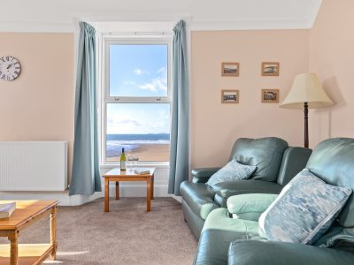 The lounge of Apartment 2 which has views over the beach and contains a comfortable leather 3 piece suite