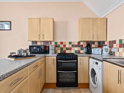 The kitchen area of Apartment 2 which contains plenty of storage, gas hob and oven, microwave, fridge freezer, washing machine & dishwasher