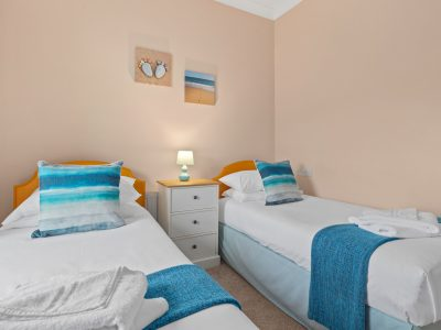 Twin bedroom of Apartment 2 with 2 beds, dressing table and wardrobe, overlooking the rear of the property