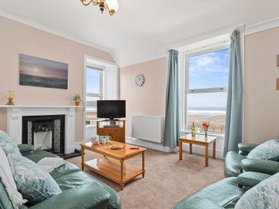 Lounge of Apartment 2 with seaview, 3 piece leather suite, TV and coffee table